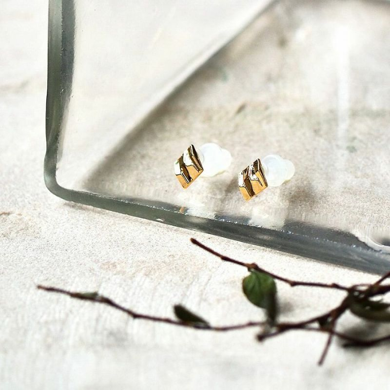 ダイヤ型のゴールドメタリックカラーのセラミックポストピアスのディスプレイ画像です。